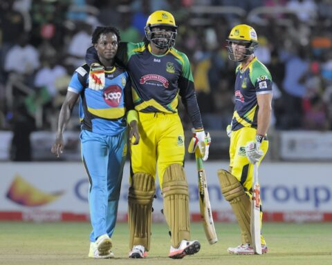 Chris Gayle (R) of Jamaica Tallawahs hug Fidel Edwards (L)