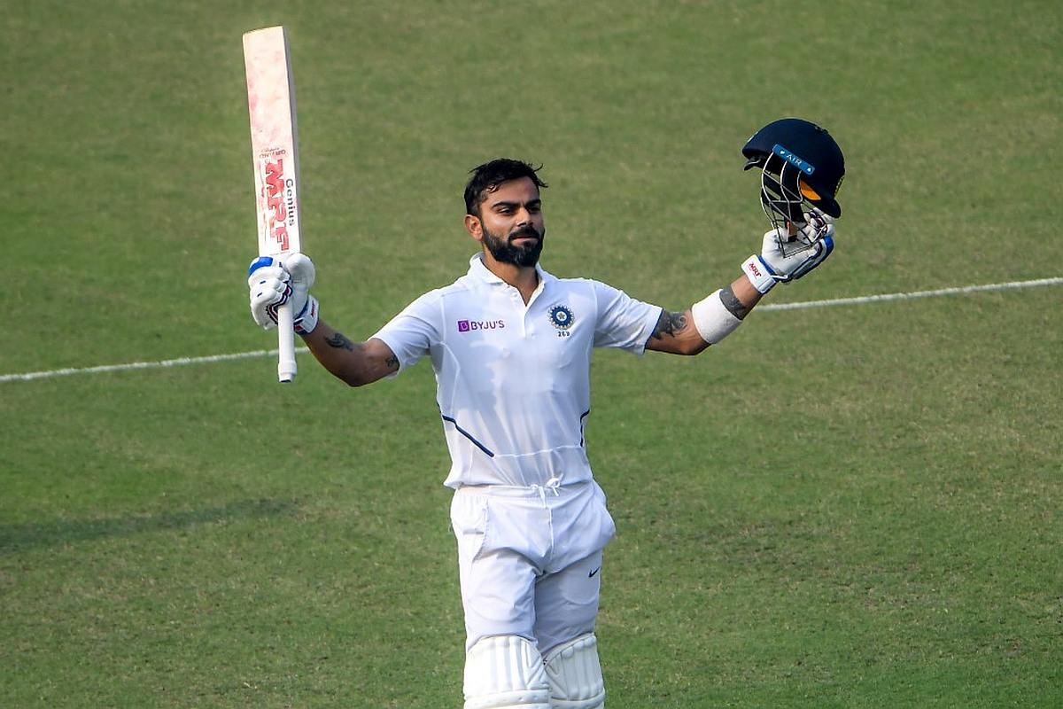 Virat Kohli celebrates his last century during the second day of the second Test cricket match of a two-match series between India and Bangladesh at the Eden Gardens cricket stadium in Kolkata on November 23, 2019. (Photo by Dibyangshu SARKAR / AFP)