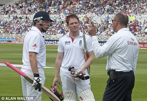An increasingly irate Ian Bell (left) and Eoin Morgan are prevented from leaving the field before tea