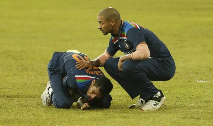 Navdeep Saini holds his arm in pain as Shikhar Dhawan attends to him, during the second Sri Lanka-India T20I on Wednesday. - AP